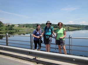 Crossing the long bridge into Portomarin with the large reservoir of Belesar behind them.